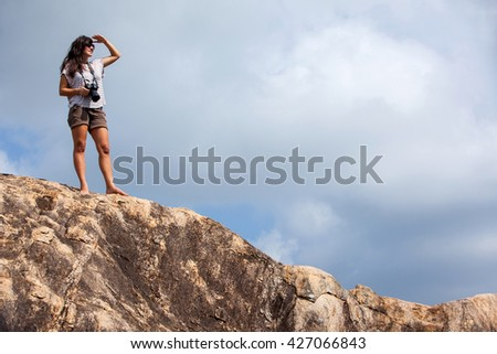Woman with a photo camera enjoys the beauty of nature hiking in the mountain peak   - stock photo