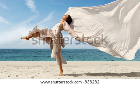 Woman with a pink scarf on the beach - stock photo