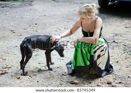 Woman with a poor stray dog - stock photo