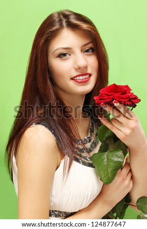 Woman with a rose on a green background - stock photo