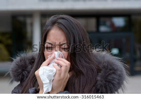 Woman with a seasonal winter cold and flu standing outdoors on an urban street in a furry jacket blowing her nose on a handkerchief - stock photo
