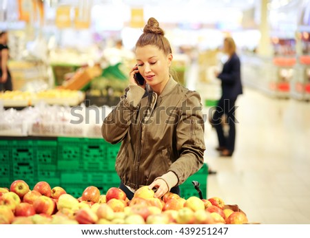 Woman with a smartphone  choosing vegetables at the market - stock photo