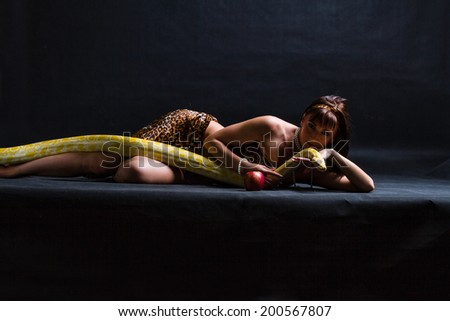 Woman with a snake eating red apple on black - stock photo