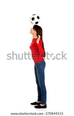 Woman with a soccer ball on head. - stock photo