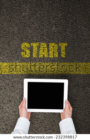 woman with a tablet on a tarmac road with yellow print of the word start for the concept of starting point. - stock photo