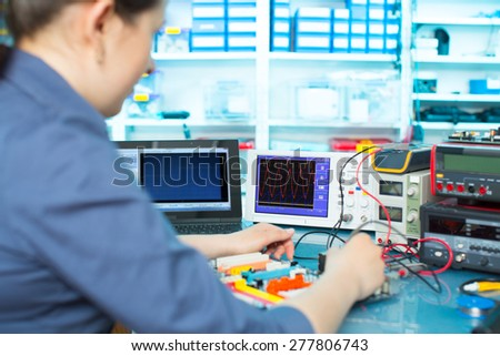 Woman with a tester and a printed circuit board - stock photo