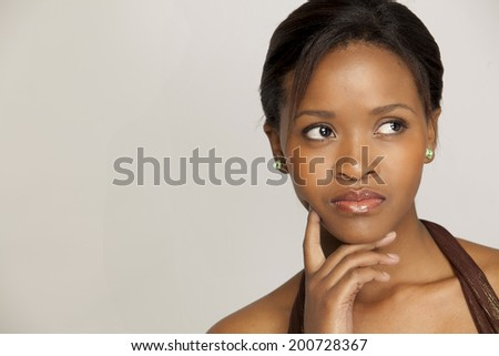 Woman with a thoughtful expression, looking away from camera. - stock photo