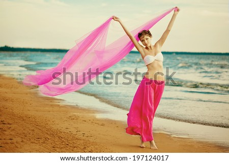 Woman with a tissue in his hands on the beach near the water - stock photo