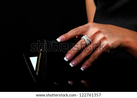 Woman with a wallet isolated on black background - stock photo