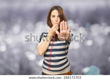 Woman with a whistle doing the stop gesture. Over abstract background - stock photo