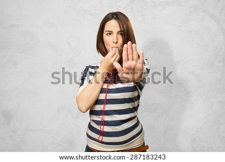 Woman with a whistle doing the stop gesture. Over concrete background - stock photo