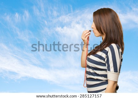 Woman with a whistle. Over clouds background - stock photo