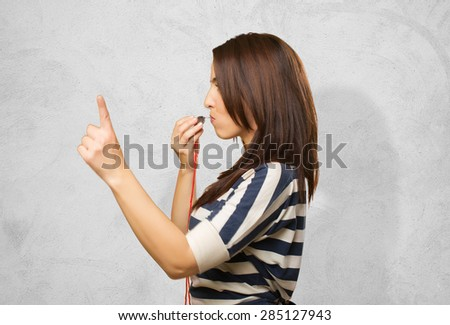 Woman with a whistle pointing with her finger. Over concrete background - stock photo