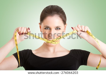 Woman with a yellow measuring tape around her mouth, isolated in green - stock photo
