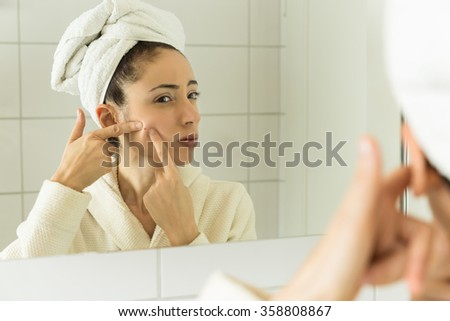 Woman with acne problem looking to mirror - stock photo