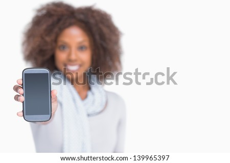 Woman with afro showing her smartphone to camera on white background - stock photo