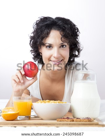 Woman with an apple on white background. Smiling cute woman having breakfast of fruit, milk, cereals, orange juice, toast. Girl looking at camera while holding an apple. Concept of nutrition and diet. - stock photo