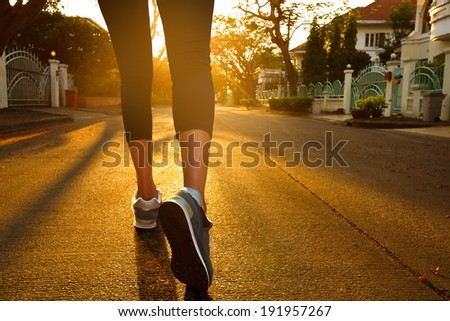 Woman with an athletic pair of legs going for a jog during sunset - stock photo