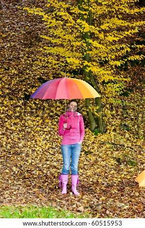 woman with an umbrella in autumnal nature - stock photo