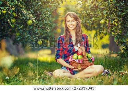 Woman with apples in the garden. Young attractive woman with a full basket of ripe red and green apples is sitting on the grass in the apple garden and smiling. Harvest season. Country lifestyle. - stock photo