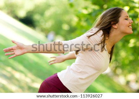 Woman with arms open enjoying nature at the park - stock photo