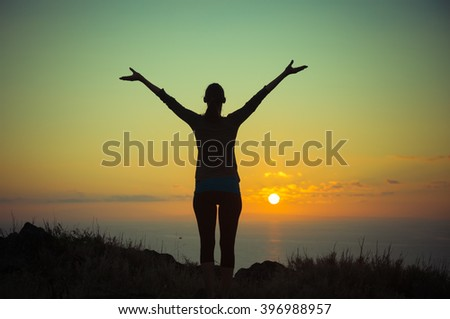 Woman with arms open taking in the beautiful view.  - stock photo