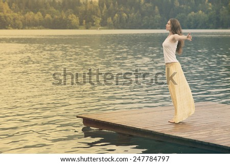 Woman with arms outstratched at lake Bled, Slovenia - stock photo