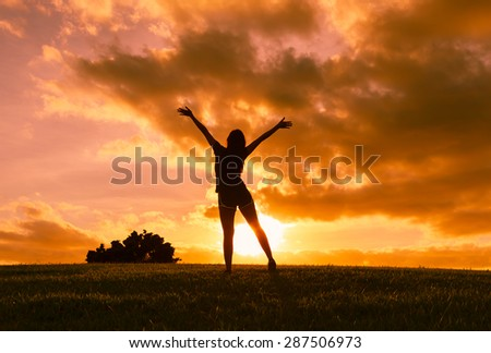 Woman with arms outstretched enjoying a beautiful sunset.  - stock photo