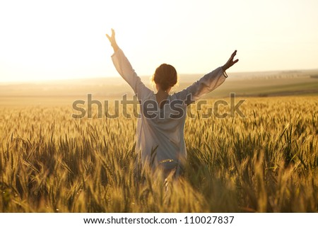 Woman with arms outstretched in a wheat field - stock photo