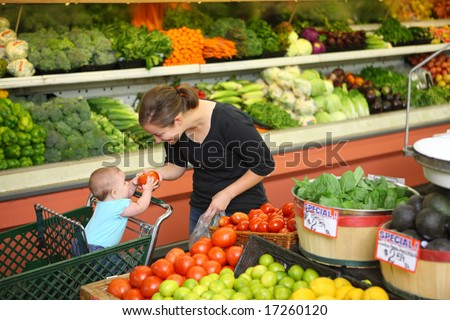 Woman with baby in produce section - stock photo