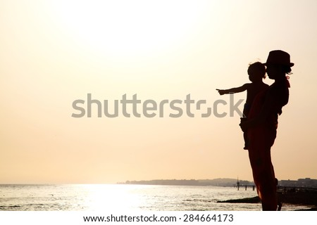Woman with baby on the beach at the sunset - stock photo