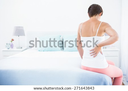 Woman with back pain at home in the bedroom - stock photo