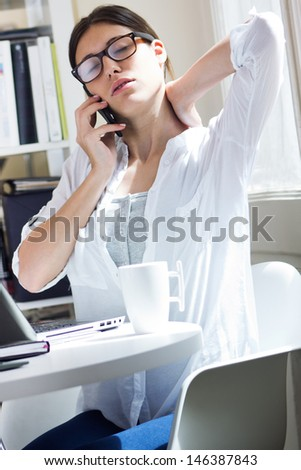 Woman with back pain at work - stock photo