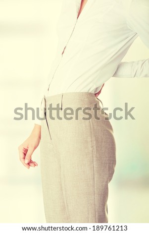 Woman with back pain holding her aching hip  - stock photo