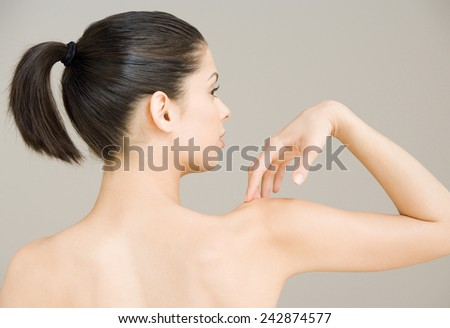 Woman with backache from behind - stock photo
