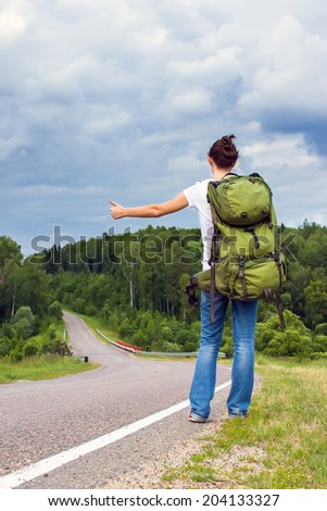 Woman with backpack hitchhiking on a country road - stock photo