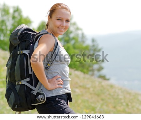 Woman with backpack on green hill. - stock photo