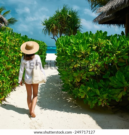 Woman with bag and sun hat going to the beach - stock photo