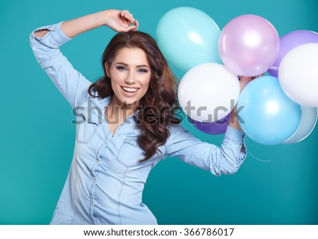 Woman with balloons in studio on a blue background - stock photo