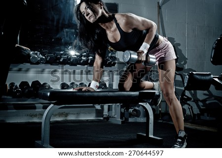 Woman with barbells in the gym - stock photo