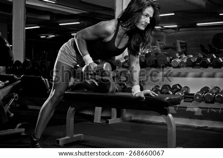 Woman with barbells in the gym - black and white - stock photo