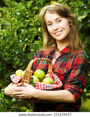 Woman with basket full of ripe apples in a garden. Young smiling attractive woman is standing with full basket of organic apples in a orchard. Country happy lifestyle concept.  - stock photo