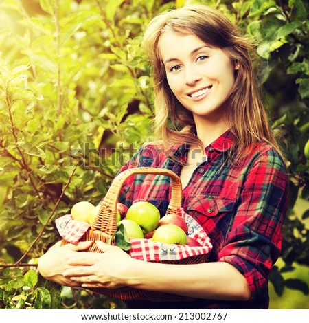 Woman with basket of apples in a garden. Young smiling attractive woman is standing with full basket of organic ripe apples in a sunlit orchard. Country happy lifestyle concept. Harvest season. - stock photo