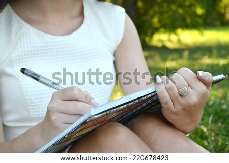 Woman with beautiful hands writing in her diary - stock photo