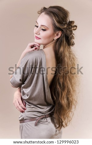 Woman with beautiful long hairstyle very sensuality. Posing in studio - stock photo