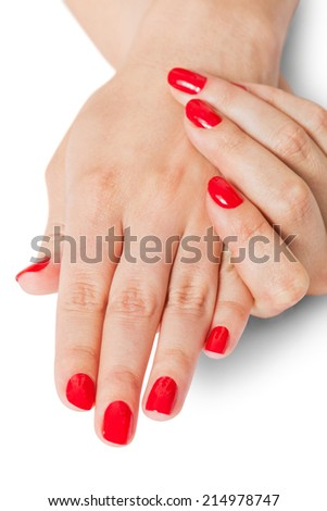 Woman with beautiful manicured red fingernails gracefully crossing her hands to display them to the viewer on a white background in a fashion, glamour and beauty concept - stock photo