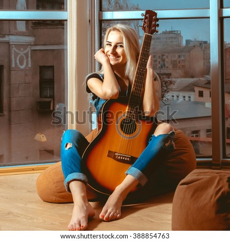 Woman with beautiful smile looking at the camera and hugging a guitar. Girl with guitar. Woman playing guitar. leisure with guitar. - stock photo
