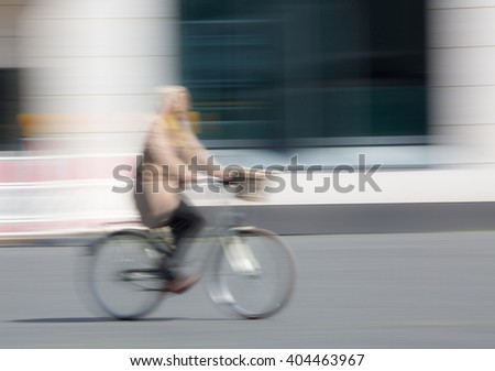 Woman with bicycle in the city, out of focus placed in motion with Copy Space - stock photo