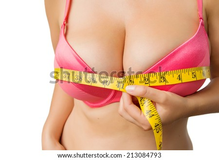 Woman with big boobs measuring her bust - stock photo