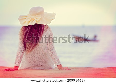 Woman with big hat looking to sea processed in vintage style - stock photo